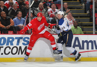 DETROIT, MI - JANUARY 23:  Jonathan Ericsson #52 of the Detroit Red Wings battles with Jason Arnott #44 of the St. Louis Blues during their NHL game at Joe Louis Arena on January 23, 2012 in Detroit, Michigan.  (Photo by Dave Sandford/Getty Images)