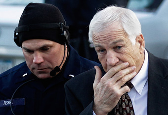 BELLEFONTE, PA - DECEMBER 13: A police officer walks with former Penn State assistant football coach, Jerry Sandusky as he arrives at the Centre County Courthouse on December 13, 2011 in Bellefonte, Pennsylvania. Sandusky who was charged with sexual abuse