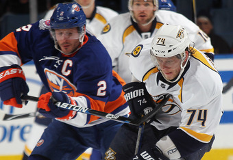UNIONDALE, NY - JANUARY 16: Mark Streit #2 of the New York Islanders gets the stick into Sergei Kostitsyn #74 of the Nashville Predators at the Nassau Veterans Memorial Coliseum on January 16, 2012 in Uniondale, New York. The Predators defeated the Island
