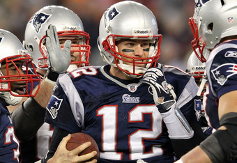 FOXBORO, MA - JANUARY 22:  Tom Brady #12 of the New England Patriots celebrates with his teammates after scoring a touchdown in the fourth quarter against the Baltimore Ravens during their AFC Championship Game at Gillette Stadium on January 22, 2012 in F