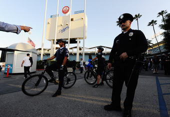LOS ANGELES, CA - APRIL 14:  Los Angeles Police Department officers stand watch at an entrance to Dodger Stadium prior to the start of the baseball game between the St. Louis Cardinals and Los Angeles Dodgers on April 14, 2011 in Los Angeles, California.