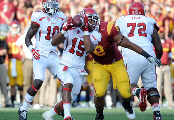 LOS ANGELES, CA - SEPTEMBER 10: John White #15 of the Utah Utes catches a pass in front of Nick Perry #8 of the USC Trojans at Los Angeles Memorial Coliseum on September 10, 2011 in Los Angeles, California.  (Photo by Harry How/Getty Images)