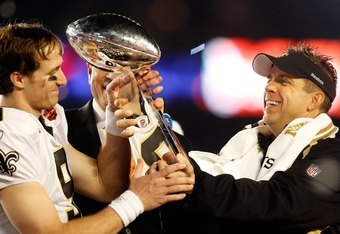 MIAMI GARDENS, FL - FEBRUARY 07:  Head coach Sean Payton of the New Orleans Saints hands quarterback Drew Brees #9 the Vince Lombardi trophy after defeating the Indianapolis Colts during Super Bowl XLIV on February 7, 2010 at Sun Life Stadium in Miami Gar