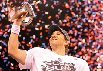 INDIANAPOLIS, IN - FEBRUARY 05:  Quarterback Eli Manning #10 of the New York Giants poses with the Vince Lombardi Trophy after the Giants defeated the Patriots by a score of 21-17 in Super Bowl XLVI at Lucas Oil Stadium on February 5, 2012 in Indianapolis