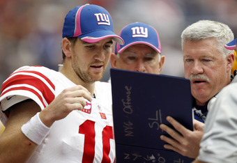 HOUSTON - OCTOBER 10:  Quarterback Eli Manning #10 of the New York Giants looks over plays with offensive coordinator Kevin Gilbride during  a football game against the Houston Texans at Reliant Stadium on October 10, 2010 in Houston, Texas.  (Photo by Bo