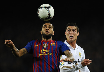BARCELONA, SPAIN - JANUARY 25:  Dani Alves of FC Barcelona (L) duels for a high ball with Cristiano Ronaldo of Real Madrid CF during the Copa del Rey quarter final second leg match between FC Barcelona and Real Madrid at Camp Nou on January 25, 2012 in Ba