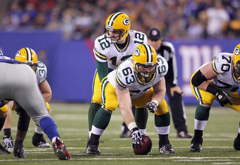 EAST RUTHERFORD, NJ - DECEMBER 04:  Aaron Rodgers #12 of the Green Bay Packers calls signals out as he stands at the line of scrimmage behind center Scott Wells #63 of the Green Bay Packers against the New York Giants at MetLife Stadium on December 4, 201