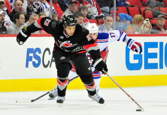 RALEIGH, NC - DECEMBER 01:  Anthony Stewart #13 of the Carolina Hurricanes moves the puck up the ice as Brandon Dubinsky #17 of the New York Rangers defends during play at the RBC Center on December 1, 2011 in Raleigh, North Carolina.  (Photo by Grant Hal