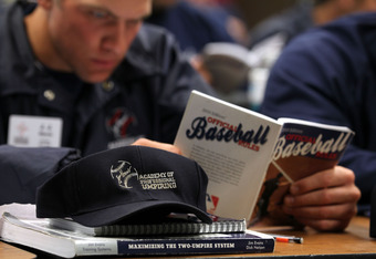A student refers to his rules book during an exam at the Jim Evans Academy for Professional Umpiring.