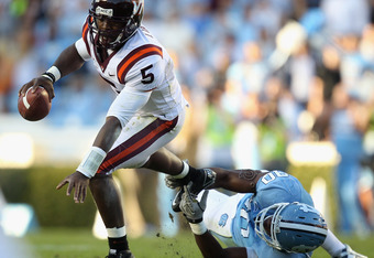 CHAPEL HILL, NC - NOVEMBER 13:  Tyrod Taylor #5 of the Virginia Tech Hokies tries to get away from Quinton Coples #90 of the North Carolina Tar Heels during their game at Kenan Stadium on November 13, 2010 in Chapel Hill, North Carolina.  (Photo by Street