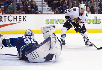 VANCOUVER, CANADA - JANUARY 31: Goalie Cory Schneider #35 of the Vancouver Canucks scrambles back to his net to stop Brendan Morrison #17 of the Chicago Blackhawks during the second period in NHL action on January 31, 2012 at Rogers Arena in Vancouver, Br