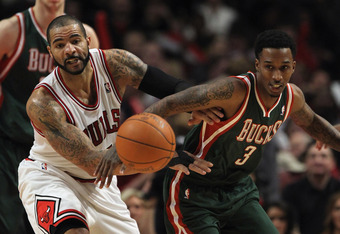 CHICAGO, IL - JANUARY 27:  Carlos Boozer #5 of the Chicago Bulls and Brandon Jennings #3 of the Milwaukee Bucks chase a loose ball at the United Center on January 27, 2012 in Chicago, Illinois. The Bulls defeated the Bucks 107-100. NOTE TO USER: User expr