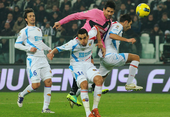 TURIN, ITALY - FEBRUARY 18:  Marco Borriello of Juventus FC in competes for a high ball with Giuseppe Bellusci (L) and Francesco Lodi (R) of Catania Calcio during the Serie A match between Juventus FC and Catania Calcio at Juventus Arena on February 18, 2