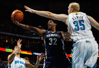 NEW ORLEANS, LA - JANUARY 18:  O.J. Mayo #32 of the Memphis Grizzlies shoots the ball around Chris Kaman #35 of the New Orleans Hornets at New Orleans Arena on January 18, 2012 in New Orleans, Louisiana.  NOTE TO USER: User expressly acknowledges and agre