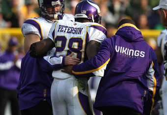 GREEN BAY, WI - NOVEMBER 11: Adrian Peterson #28 of the Minnesota Vikings is helped from the field after suffering an injury against the Green Bay Packers on November 11, 2007 at Lambeau Field in Green Bay, Wisconsin. The Packers defeated the Vikings 34-0