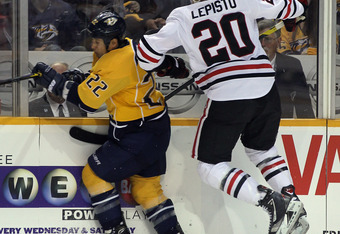 NASHVILLE, TN - FEBRUARY 14: Sami Lepisto #20 of the Chicago Blackhawks hits Jordin Tootoo #22 of the Nashville Predators into the boards during the second period at the Bridgestone Arena on February 14, 2012 in Nashville, Tennessee.  (Photo by Bruce Benn