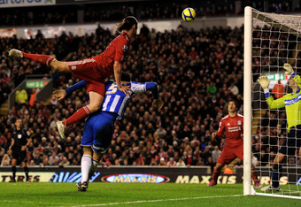 LIVERPOOL, ENGLAND - FEBRUARY 19:   Andy Carroll of Liverpool provides an assist for Luis Suarez to score his team's sixth goal during the FA Cup Fifth Round match between Liverpool and Brighton & Hove Albion at Anfield on February 19, 2012 in Liverpool,