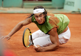 PARIS - JUNE 05:  Rafael Nadal of Spain falls to the floor against Mariano Puerta of Argentina during the Mens Final match on the fourteenth day of the French Open at Roland Garros on June 5, 2005 in Paris, France.  (Photo by Clive Mason/Getty Images)