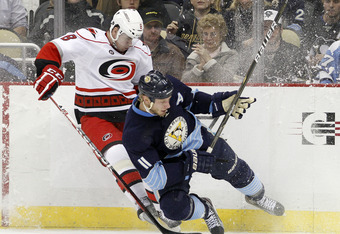 PITTSBURGH, PA - DECEMBER 27:  Jordan Staal #11 of the Pittsburgh Penguins and Jaroslav Spacek #8 of the Carolina Hurricanes battle for a puck in the corner during the game at Consol Energy Center on December 27, 2011 in Pittsburgh, Pennsylvania.  (Photo