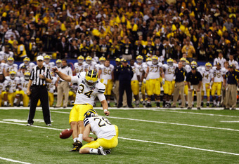 NEW ORLEANS, LA - JANUARY 03:  Brendan Gibbons #34 of the Michigan Wolverines kicks a successful 37-yard game-winning field goal attempt in overtime from the hold of  Drew Dileo #26 against the Virginia Tech Hokies  during the Allstate Sugar Bowl at Merce