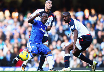 LONDON, ENGLAND - FEBRUARY 25:  Michael Essien of Chelsea is challenged from behind by Darren Pratley of Bolton Wanderers during the Barclays Premier League match between Chelsea and Bolton Wanderers at Stamford Bridge on February 25, 2012 in London, Engl
