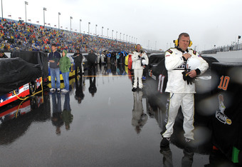 DAYTONA BEACH, FL - FEBRUARY 26:  A NASCAR official stands on the grid during the national anthem as it rains prior to the start of the NASCAR Sprint Cup Series Daytona 500 at Daytona International Speedway on February 26, 2012 in Daytona Beach, Florida.