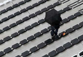 DAYTONA BEACH, FL - FEBRUARY 26:  A race fan stands with an umbrella in the grandstands during a rain delayed start in the NASCAR Sprint Cup Series Daytona 500 at Daytona International Speedway on February 26, 2012 in Daytona Beach, Florida.  (Photo by Je