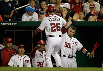 WASHINGTON, DC - AUGUST 18: Jesus Flores #26 of the Washington Nationals is congratulated by Jonny Gomes #30 after scoring a Cincinnati Reds at Nationals Park on August 18, 2011 in Washington, DC.  (Photo by Rob Carr/Getty Images)