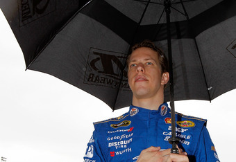 DAYTONA BEACH, FL - FEBRUARY 26:  Brad Keselowski, driver of the #2 Miller Lite Dodge, stands on the grid for the national anthem in the rain prior to the start of the NASCAR Sprint Cup Series Daytona 500 at Daytona International Speedway on February 26,