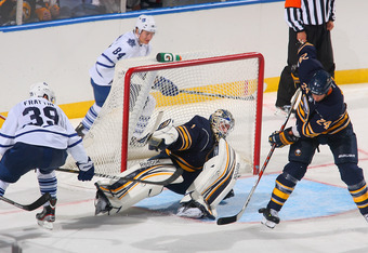 BUFFALO, NY - SEPTEMBER 24: Robin Regehr #24 of the Buffalo Sabres clears the puck after Jhonas Enroth #1 of the Sabres makes a save on Matt Frattin #39 of  the Toronto Maple Leafs at First Niagara Center on September 24, 2011 in Buffalo, New York.  (Phot