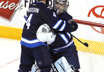 WINNIPEG, CANADA - MARCH 1: Zach Bogosian #4 of the Winnipeg Jets congratulates goaltender Ondrej Pavelec #31 after a 7-0 shutout against the Florida Panthers in NHL action at the MTS Centre on March 1, 2012 in Winnipeg, Manitoba, Canada. (Photo by Marian