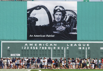 BOSTON - JULY 22:  Fans walk past a poster of Ted Williams during his military service in Korea sitting in his fighter jet hanging over the Green Monster before the Ted Williams tribute on July 22, 2002 at Fenway Park in Boston, Massachusetts. The public