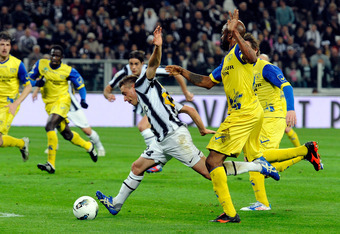 TURIN, ITALY - MARCH 03:  Emanuele Giaccherini of Juventus FC and Luciano of AC Chievo Verona compete for the ball during the Serie A match between Juventus FC and AC Chievo Verona at Juventus Arena on March 3, 2012 in Turin, Italy.  (Photo by Claudio Vil