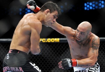 DALLAS - SEPTEMBER 19:  UFC fighter Rafael Dos Anjos (L) battles UFC fighter Rob Emerson (R) during their Lightweight bout at UFC 103: Franklin vs. Belfort at the American Airlines Center on September 19, 2009 in Dallas, Texas.  (Photo by Jon Kopaloff/Get