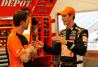 DAYTONA BEACH, FL - FEBRUARY 17:  Joey Logano, driver of the #20 The Home Depot Toyota, talks to a crew member in the garage area during practice for the NASCAR Budweiser Shootout at Daytona International Speedway on February 17, 2012 in Daytona Beach, Fl