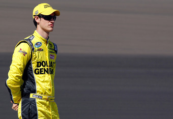 AVONDALE, AZ - MARCH 03:  Joey Logano, driver of the #20 Dollar General Toyota, looks on from the grid during qualifying for the NASCAR Nationwide Series Bashas' Supermarkets 200 at Phoenix International Raceway on March 3, 2012 in Avondale, Arizona.  (Ph