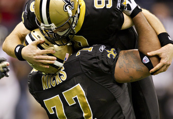 Carl Nicks celebrates with Drew Brees moments after Brees broke Dan Marino's record for single-season passing yards.