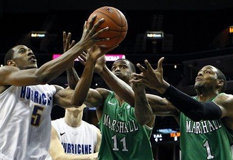 Tulsa's Tim Peete and Marshall's Nigel Spikes and Dennis Tinnon reach for a loose ball during the first half in the Conference USA men's basketball tournament Thursday (AP Photo/The Commercial Appeal, Mark Weber)