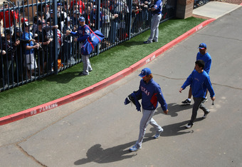PEORIA, AZ - MARCH 07:  Starting pitcher Yu Darvish #11 of the Texas Rangers walks out to the field past fans before the spring training game against the San Diego Padres at Peoria Stadium on March 7, 2012 in Peoria, Arizona.  (Photo by Christian Petersen