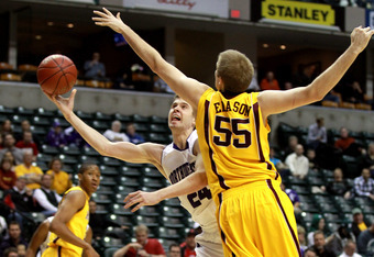INDIANAPOLIS, IN - MARCH 08:  John Shurna #24 of the Northwestern Wildcats drives for a shot attempt against Elliott Eliason #55 of the Minnesota Golden Gophers during their first round game of 2012 Big Ten Men's Basketball Conferene Tournament at Bankers