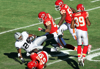KANSAS CITY, MO - DECEMBER 24:  Michael Bush #29 of the Oakland Raiders is tackled by Jovan Belcher #59, Derrick Johnson #56, and Justin Houston #50 of Kansas City Chiefs during the game on December 24, 2011 at Arrowhead Stadium in Kansas City, Missouri.