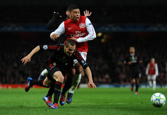 LONDON, ENGLAND - MARCH 06: Alex Oxlade-Chamberlain of Arsenal is brought down in the area by Djamel Mesbah of AC Milan to win a penalty during the UEFA Champions League Round of 16 second leg match between Arsenal and AC Milan at Emirates Stadium on Marc
