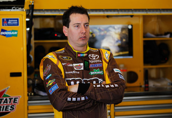 DAYTONA BEACH, FL - FEBRUARY 22:  Kyle Busch, driver of the #18 M&M's Brown Toyota, stands in the garage during practice for the NASCAR Sprint Cup Series Daytona 500 at Daytona International Speedway on February 22, 2012 in Daytona Beach, Florida.  (Photo