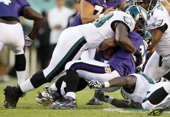 PHILADELPHIA, PA - AUGUST 11:  Trent Cole #58 of the Philadelphia Eagles tackles Ray Rice #27 of the Baltimore Ravens for a loss during their pre season game on August 11, 2011 at Lincoln Financial Field in Philadelphia, Pennsylvania.  (Photo by Jim McIsa