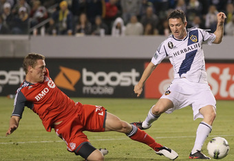 CARSON, CA - MARCH 14:  Ty Harden (L) #20 of the Toronto FC scores an own goal past Robbie Keane #7 of the Los Angeles Galaxy in the second half during a CONCACAF Champions League game at The Home Depot Center on March 14, 2012 in Carson, California. Toro