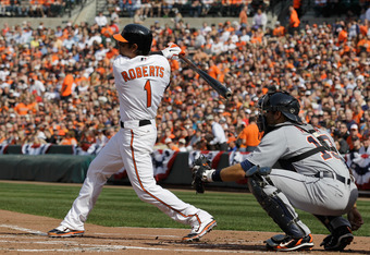 BALTIMORE, MD - APRIL 04: Brian Roberts #1 of the Baltimore Orioles swings at a pitch as catcher Alex Avila #13 of the Detroit Tigers looks on during opening day at Oriole Park at Camden Yards on April 4, 2011 in Baltimore, Maryland.  (Photo by Rob Carr/G