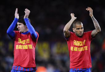 BARCELONA, SPAIN - MARCH 20:  Dani Alves of FC Barcelona (R) and his teammate Lionel Messi wear a shirt in support of Fabrice Muamba of Bolton Wanderers prior to the La Liga match between FC Barcelona and Granada CF at Camp Nou on March 20, 2012 in Barcel