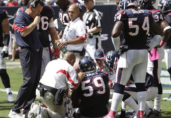 HOUSTON - OCTOBER 17:  DeMeco Ryans #59 of the Houston Texans is examined by medical staff as head coach Gary Kubiak looks on during a football game against the Kansas City Chiefs at Reliant Stadium on October 17, 2010 in Houston, Texas.  (Photo by Bob Le