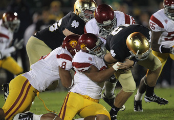 SOUTH BEND, IN - OCTOBER 22:  Andrew Hendrix #12 of the Notre Dame Fighting Irish is brought down by Wes Horton #96, George Uko #90 and Nick Perry #8 of the University of Southern California Trojans at Notre Dame Stadium on October 22, 2011 in South Bend,