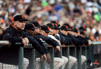 SAN FRANCISCO, CA - SEPTEMBER 10: Manager Bruce Bochy #16 and other coaches and players of the San Francisco Giants looks on from the duguout against the Los Angeles Dodgers during an MLB baseball game at AT&T Park on September 10, 2011 in San Francisco,